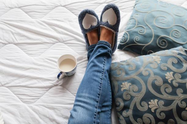 Persönliche Ansicht der Senior Inder Beine entspannen auf dem Bett mit blauen Hausschuhen während der Nachmittags-Teepause – Foto