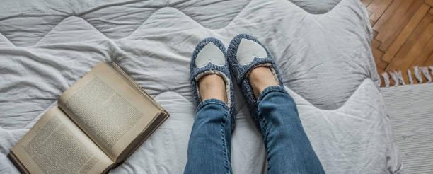 Persönliche Ansicht der Frau Beine entspannend auf dem Bett tragen blaue Hausschuhe – Foto