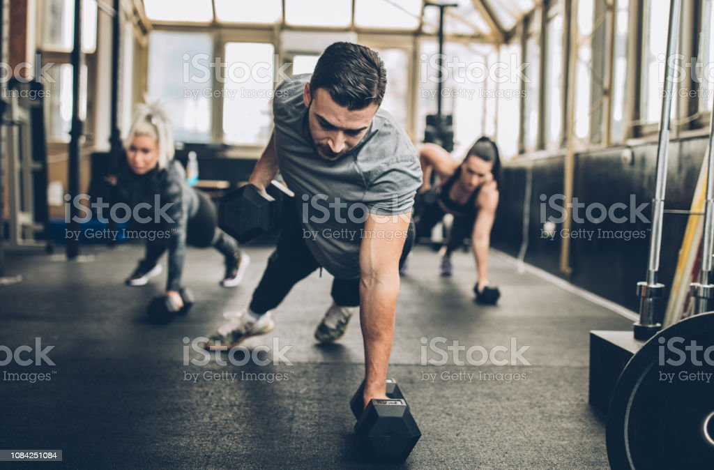 Personal Weight Training In The Gym Two young fitness women exercise with dumbbell with personal trainer in the gym Active Lifestyle Stock Photo