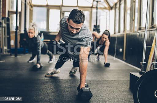 Two young fitness women exercise with dumbbell with personal trainer in the gym