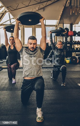 Two young fitness women exercise with weights with personal trainer in the gym