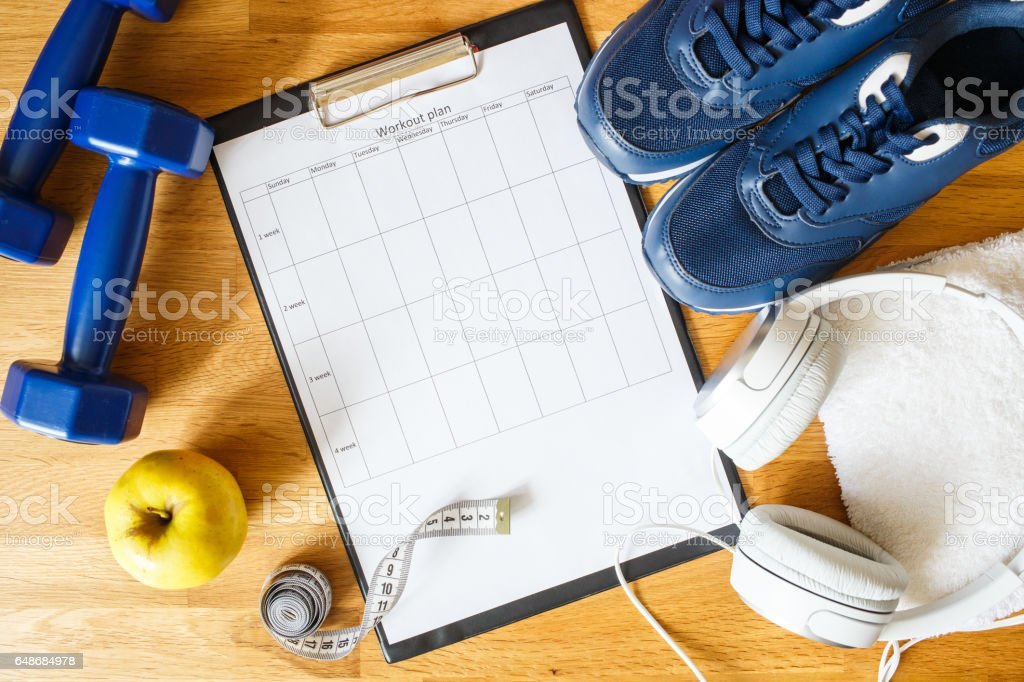 Personal workout plan with sneakers and dumbbells Personal workout plan with sneakers, headphones and dumbbells. Top view image Above Stock Photo