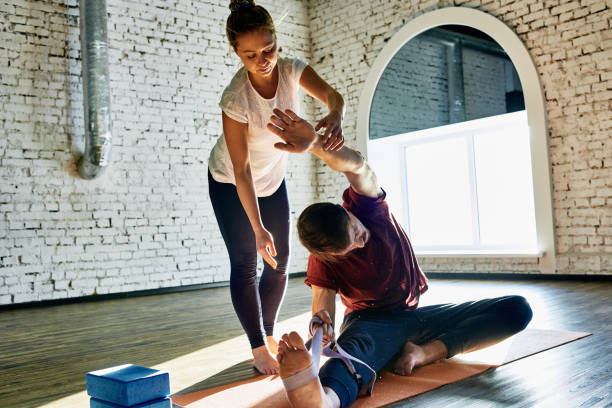 Personal yoga trainer Serious yogis training non-professional man during personal class in studio yoga instructor stock pictures, royalty-free photos & images