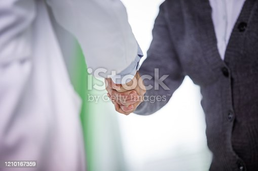 Cut out of doctor's and patient's hands shaking before doing a medical consultation where professional shows the personalized service he offers.