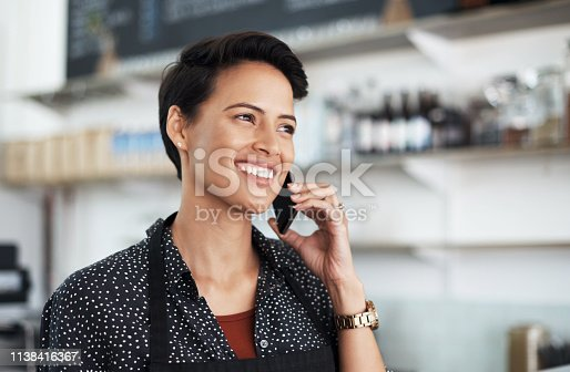 Shot of a young woman talking on her phone while working in a coffee shop