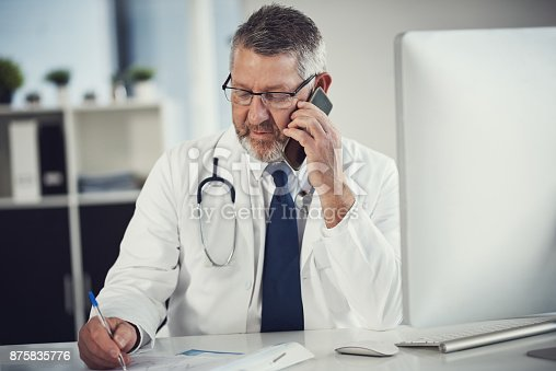 Shot of a mature doctor using a mobile phone at a desk in his office