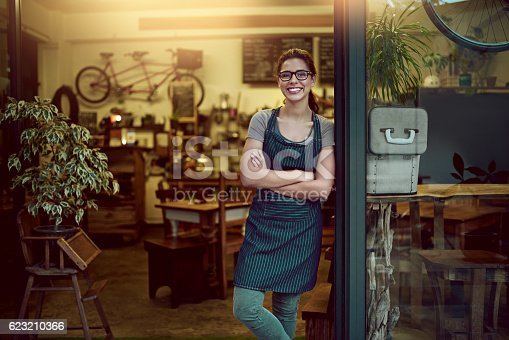 Portrait of a confident young woman standing in the doorway of a coffee shop