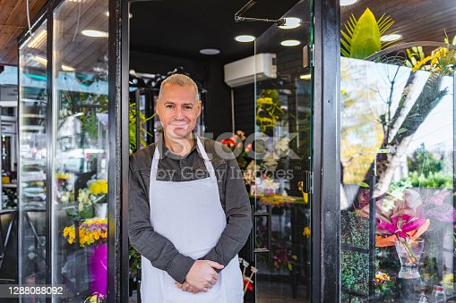 Portrait Of Male Mature Florist Standing Outside His Shop Smiling To Camera.