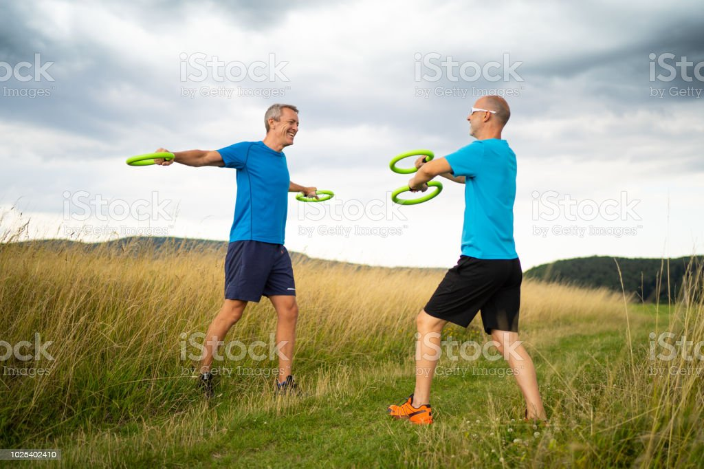 two men exercising with alternative weights during outdoor workout...