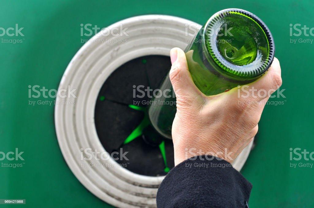 Personne mettant une bouteille en verre dans un container de recyclage stock photo