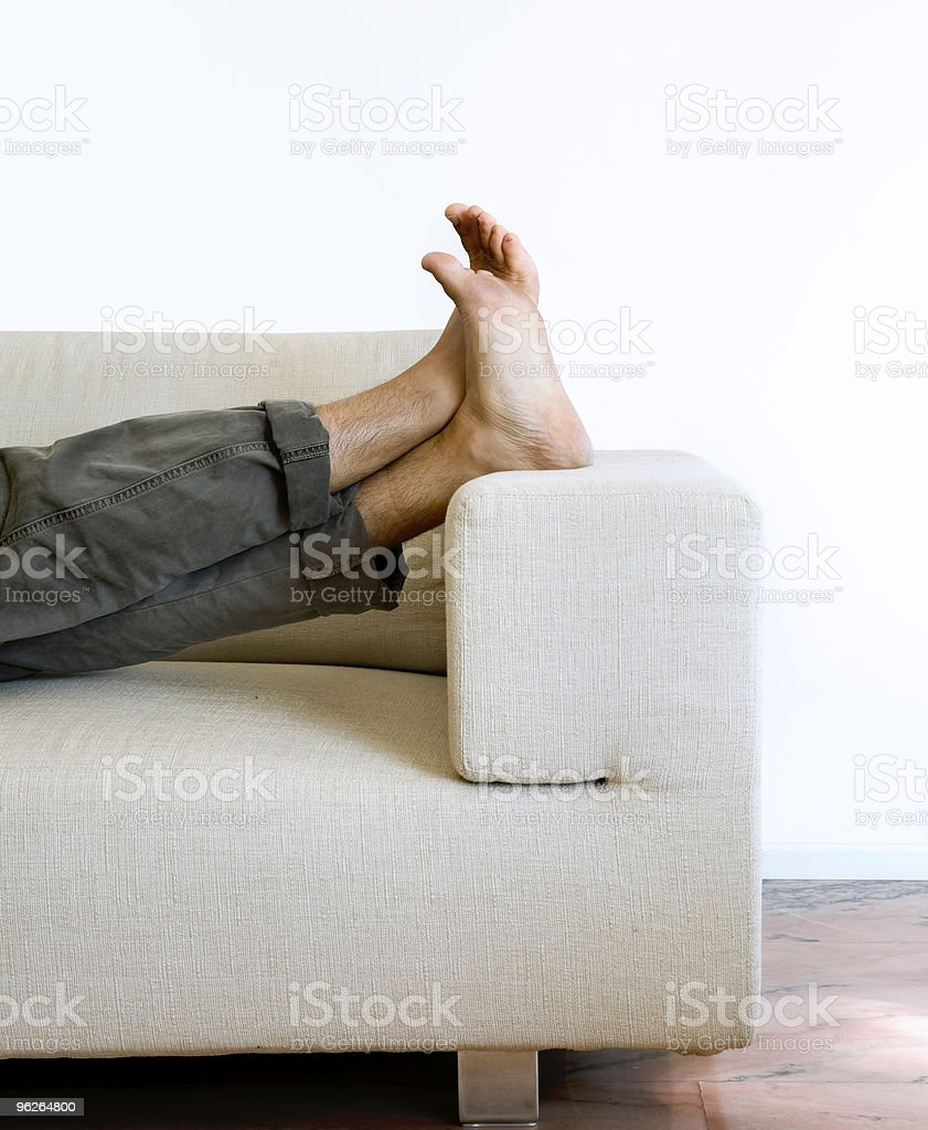 A person's bare feet laying on a couch in a modern flat royalty-free stock photo