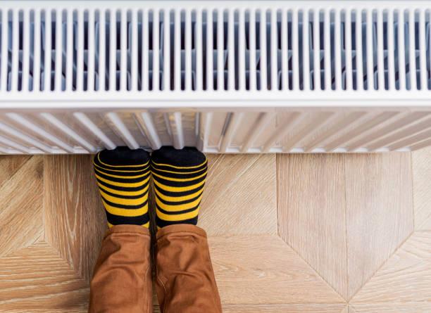 person, die füße in hellen gelb-schwarz-socken, die sie gegen einen heizkörper erwärmung. textfreiraum. - heizraum stock-fotos und bilder