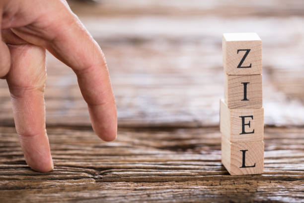 Person's Finger Walking Towards Ziel (Goal in German) Word Close-up Of A Person's Finger And Stacked Ziel (Goal in German) Word From Wooden Blocks ziel stock pictures, royalty-free photos & images
