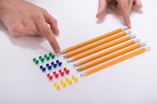 Person's Hand Arranging Pencils And Multi Colored Pushpins stock photo