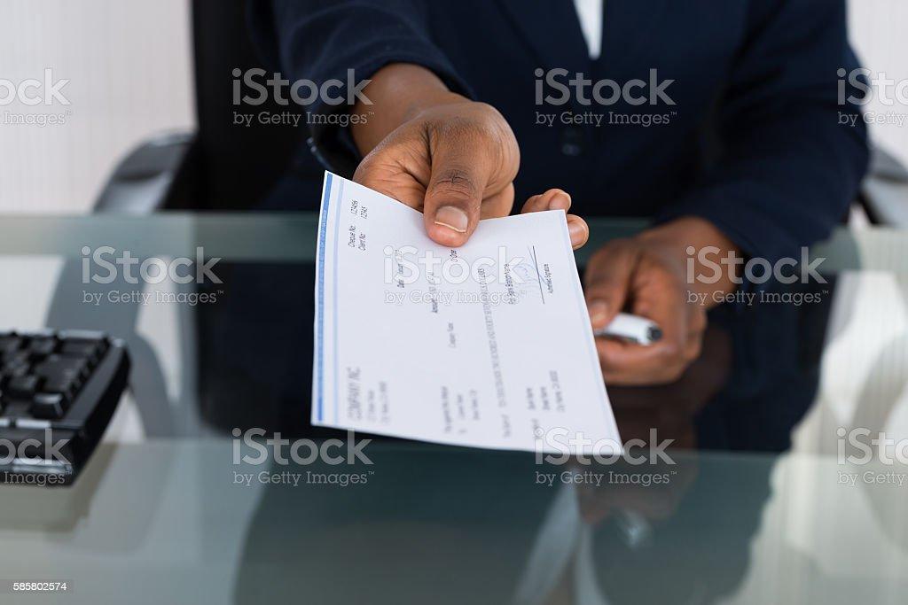 Person's Hand Giving Cheque - foto stock