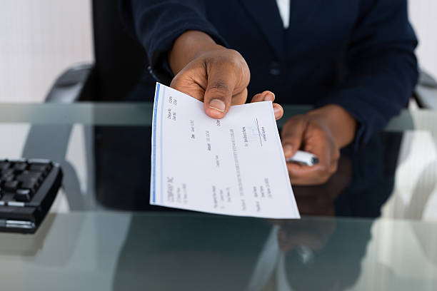 person's hand giving cheque - blank check stock photos and pictures