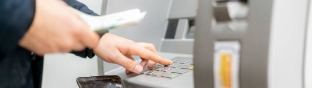 persons hand hold a wallet with cash and withdraw some money in atm stock photo