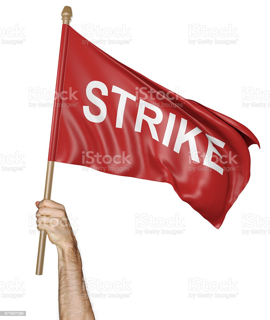 Person's hand holding a waving flag with the word strike stock photo