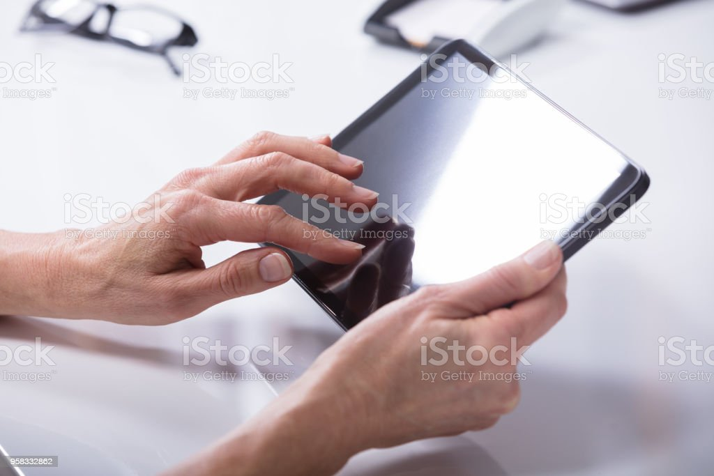 Person's Hand Holding Digital Tablet stock photo