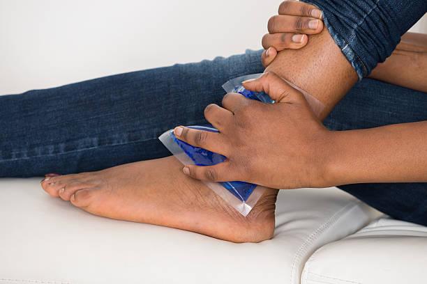person's hand holding ice gel pack on ankle - caviglia foto e immagini stock