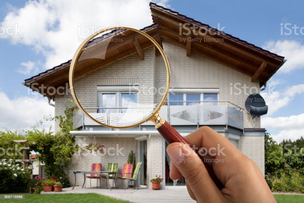 Person's Hand Holding Magnifying Glass Over Luxury House stock photo