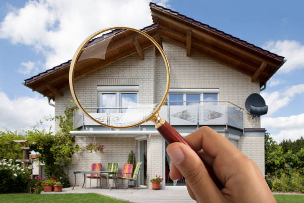 person's hand holding magnifying glass over luxury house - esaminare foto e immagini stock