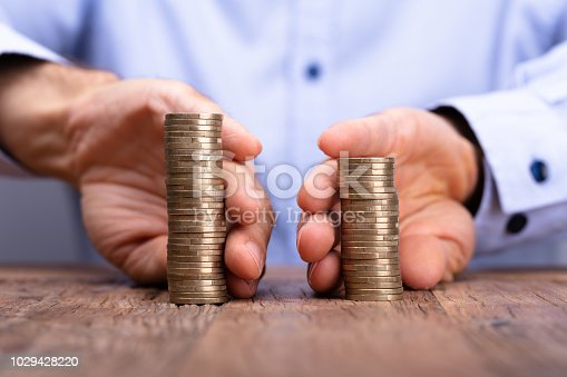 Close-up Of A Person's Hand Holding Stack Of Coins