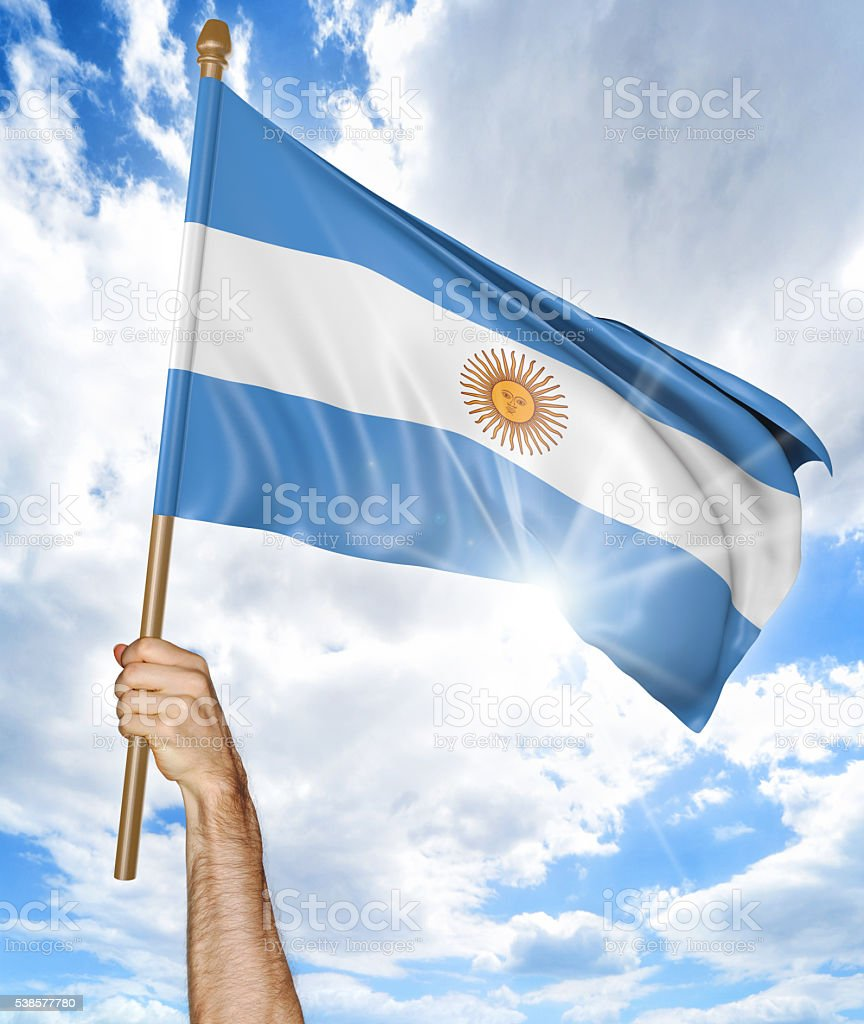 Person's hand holding the Argentine national flag and waving it stock photo