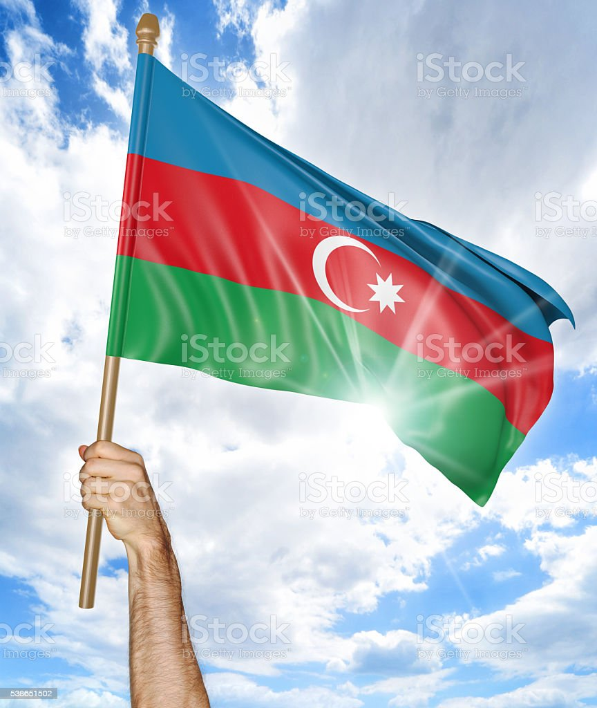Person's hand holding the Azerbaijan national flag and waving it stock photo