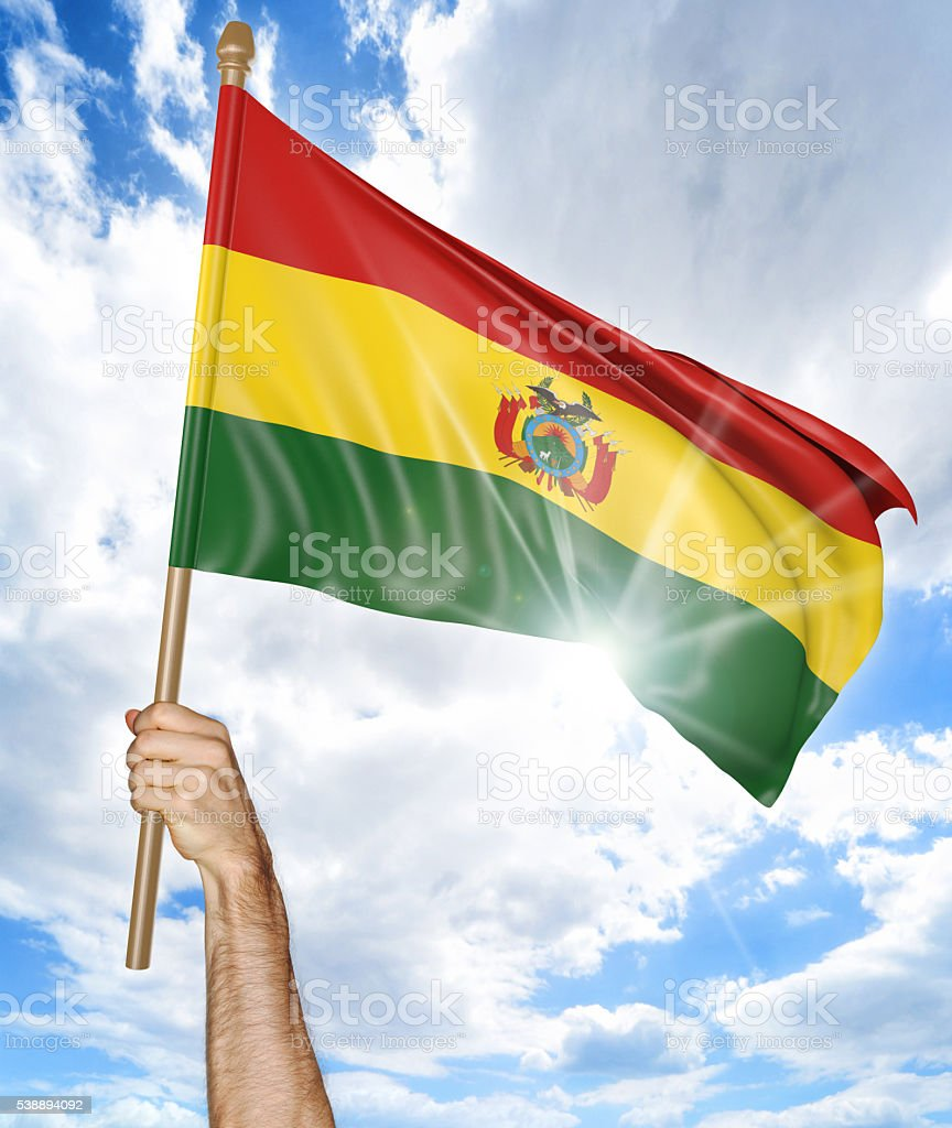 Person's hand holding the Bolivian national flag and waving it stock photo