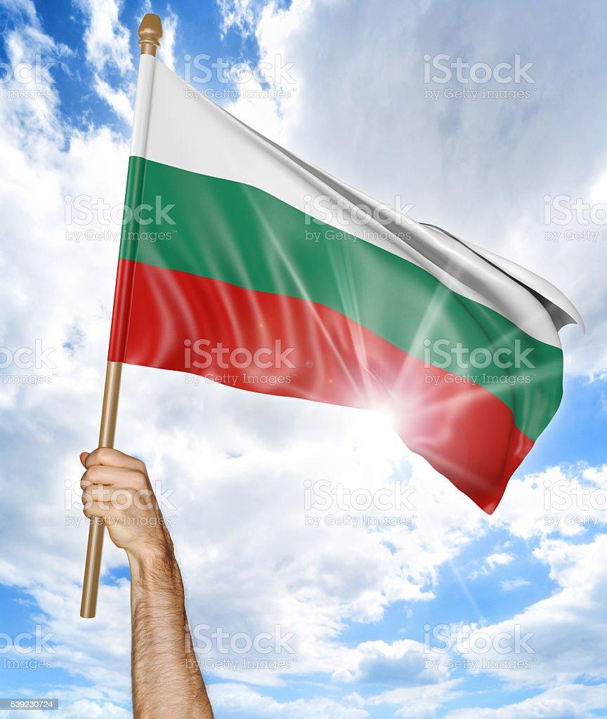 Persona mano sosteniendo la bandera nacional de Bulgaria y agitando su foto de stock libre de derechos