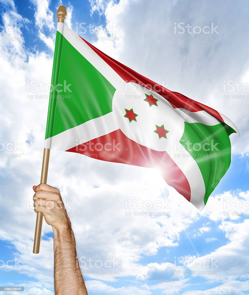 Person's hand holding the Burundi national flag and waving it stock photo