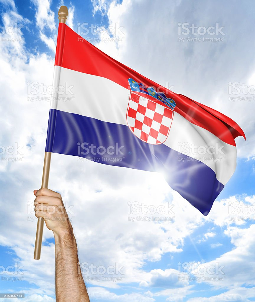 Person's hand holding the Croatian national flag and waving it stock photo