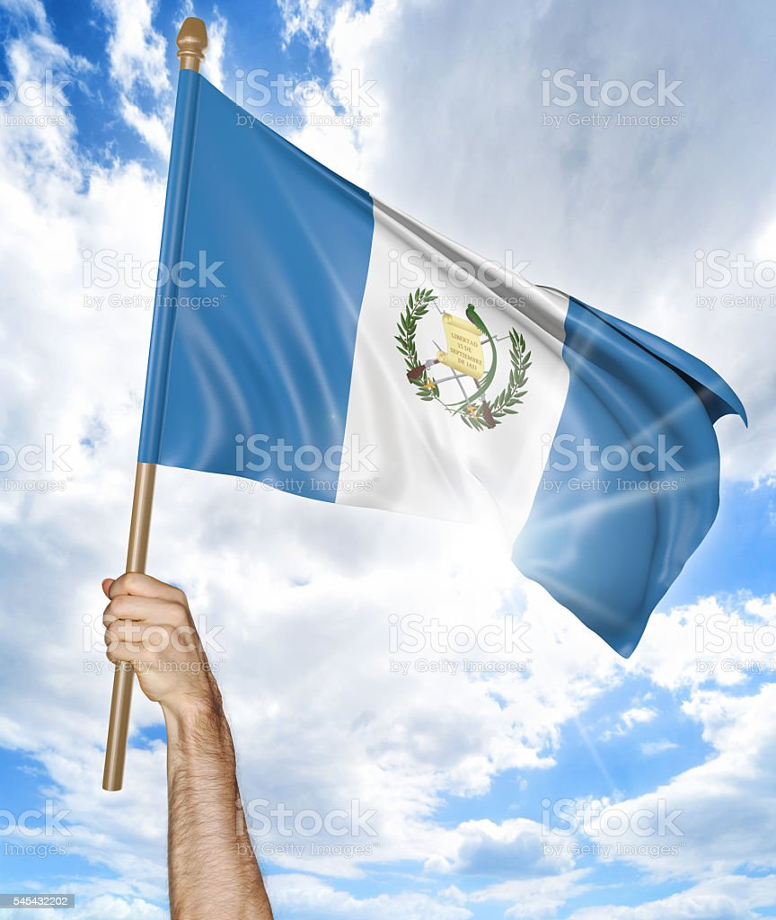 Person's hand holding the Guatemalan national flag and waving it stock photo