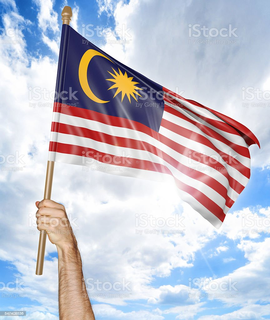 Person's hand holding the Malaysian national flag and waving it - foto de acervo