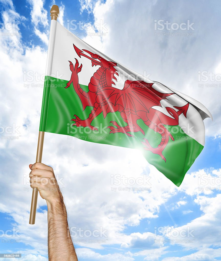 Person's hand holding the Welsh national flag and waving it stock photo