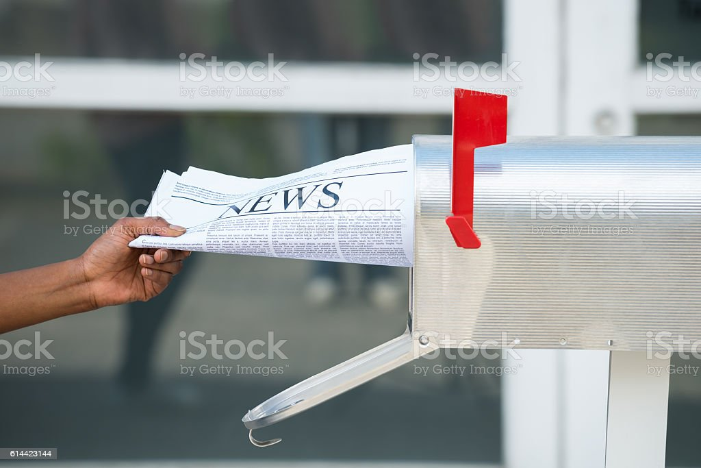 Person's Hand Opening Mailbox To Remove Newspaper stock photo