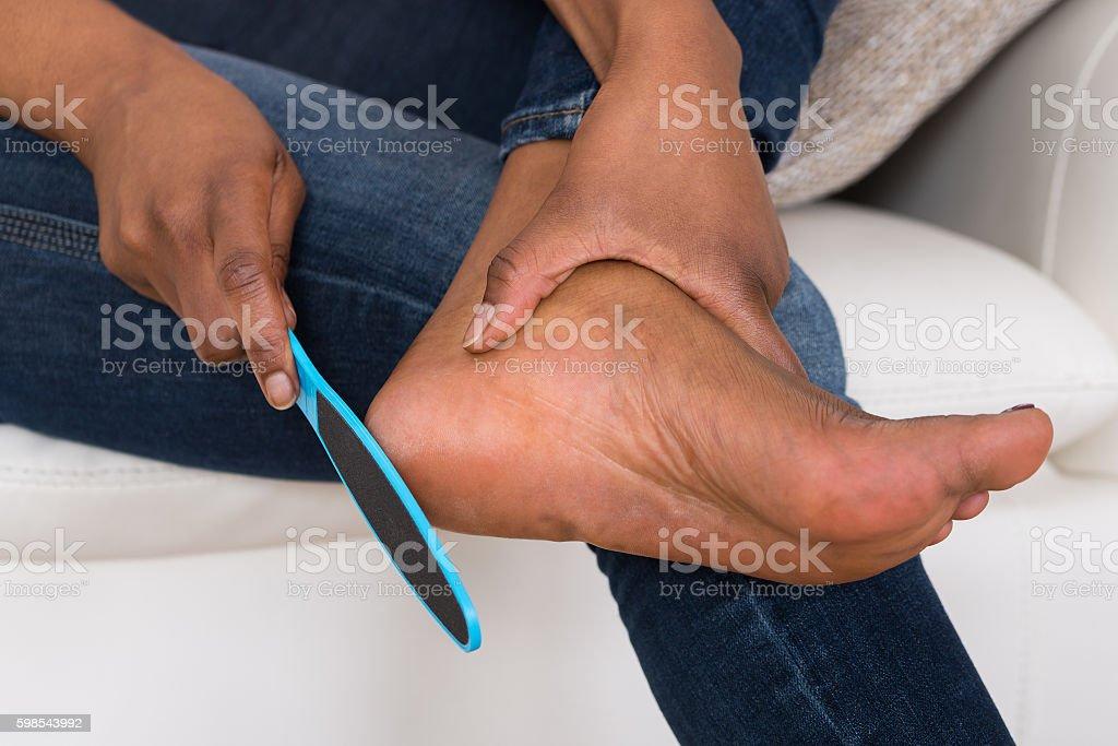 Person's Hand Pedicuring Her Legs photo libre de droits