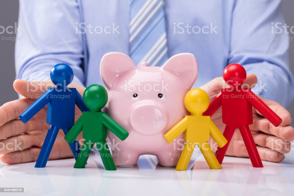 Person's Hand Protecting Piggybank And Human Figures stock photo