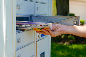Person's hand pulling a pile of junk mail out of a community mailbox