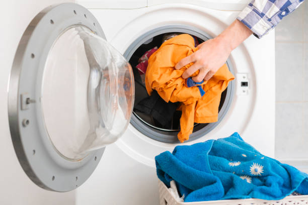 persons hand put dirty clothes in the washing machine b stock photo