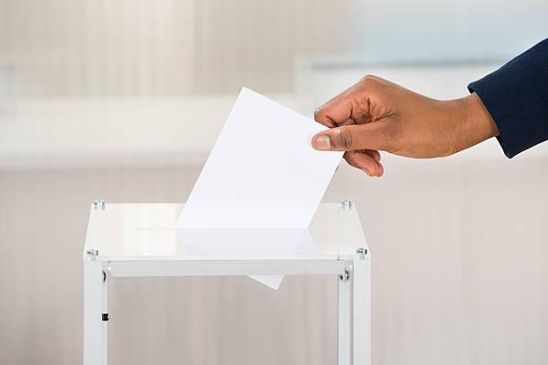 person's hand putting ballot in box - voting hands stockfoto's en -beelden