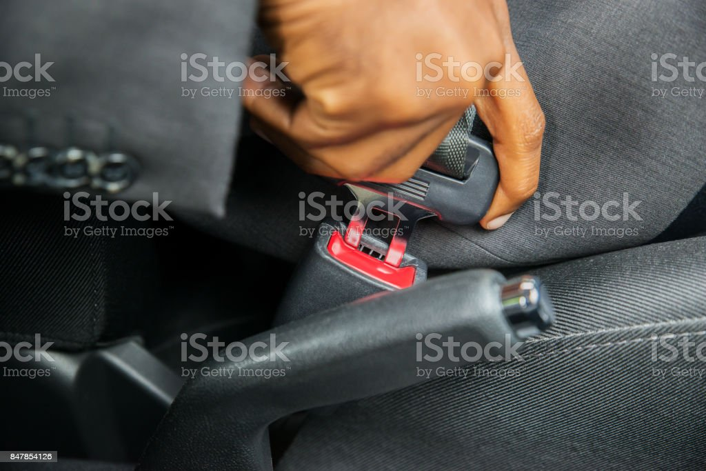 Person's Hand Sitting In Car Fastening Seat Belt stock photo