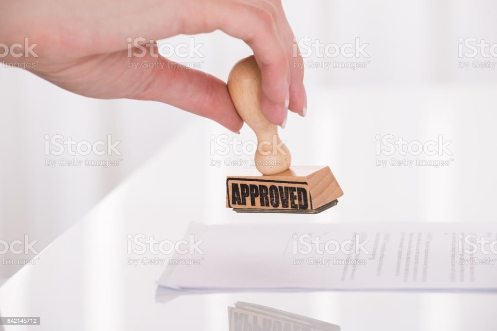 Person's Hand Stamping Approved On Contract Paper stock photo