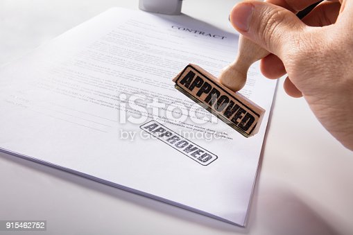 854317150istockphoto Person's Hand Stamping Approved On Contract Paper 915462752