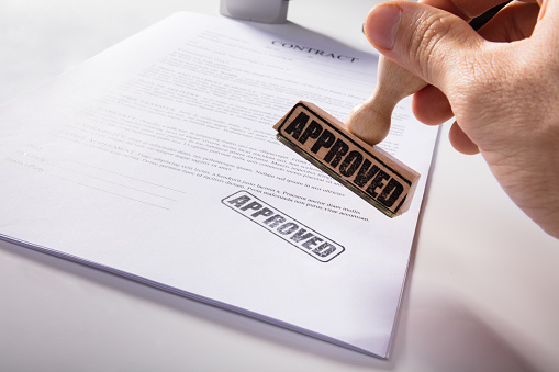 854317150 istock photo Person's Hand Stamping Approved On Contract Paper 915462752