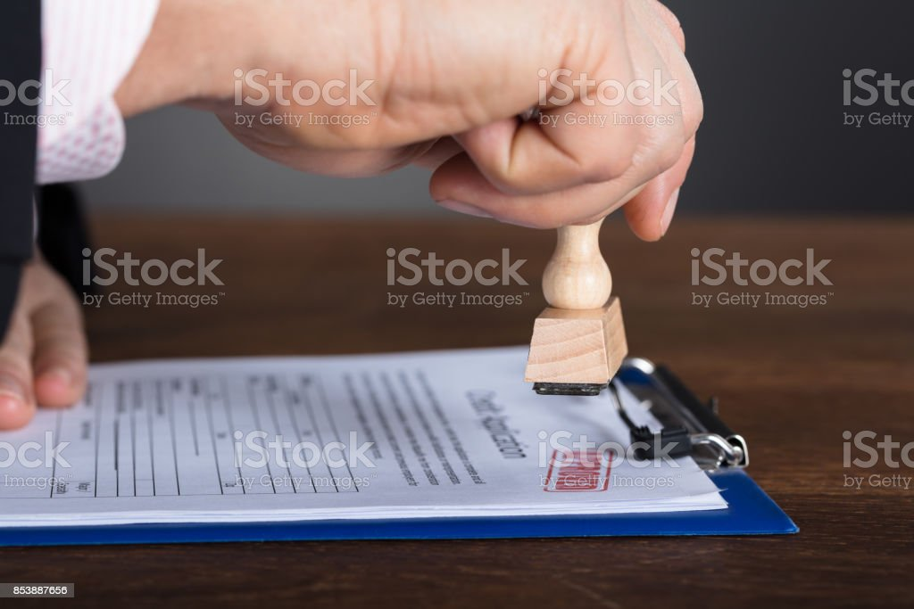 Person's Hand Stamping On Approved Form stock photo