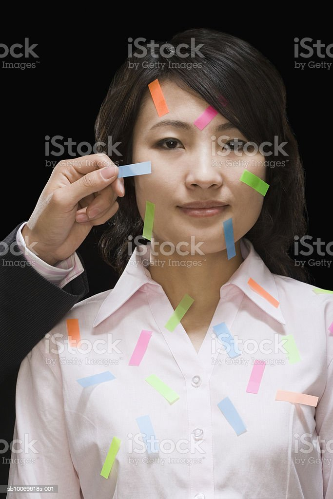 Person's hand sticking multi-colored adhesive tapes on woman's face royalty-free stock photo