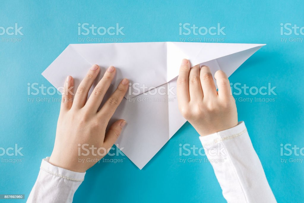 Person's hands folding a paper airplane stock photo