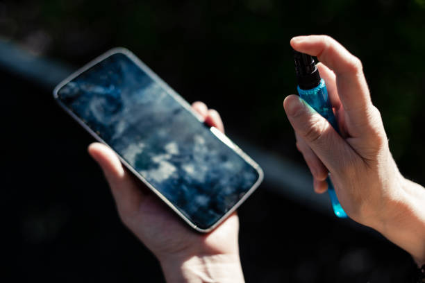 Person's hands holding and cleaning a mobile phone screen stock photo